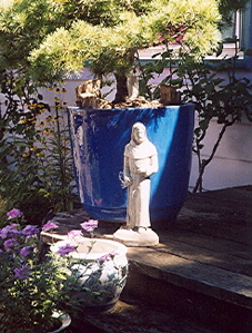 Statue of Saint Fiacre standing by a larg, blue, ceramic pot with a little pine tree in it